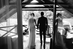 De bruid en de bruidegom op het balkon in de hotelruimte royalty-vrije stock foto