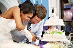 De bruid en de bruidegom snijden de huwelijkscake Stock Foto