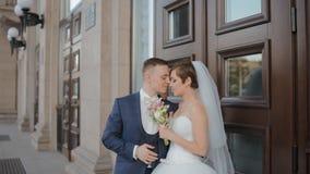 De bruid en de bruidegom stellen aan fotograaf openlucht stock footage