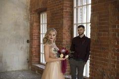 De bruid en de bruidegom stellen dichtbij venster en uitstekende bakstenen muur Royalty-vrije Stock Foto's