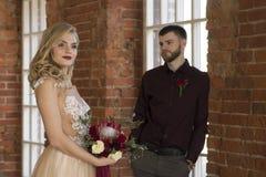 De bruid en de bruidegom stellen dichtbij venster en uitstekende bakstenen muur Stock Foto's