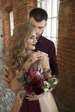 De bruid en de bruidegom stellen dichtbij venster en uitstekende bakstenen muur Royalty-vrije Stock Fotografie