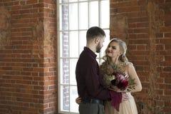 De bruid en de bruidegom stellen dichtbij venster en uitstekende bakstenen muur Royalty-vrije Stock Foto