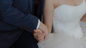 De bruid en de bruidegom stellen holdingshanden stock footage