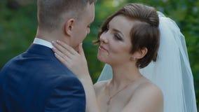 De bruid en de bruidegom stellen openlucht met natuurlijk licht stock videobeelden