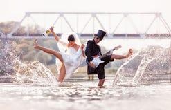 De bruid en de bruidegom zijn gelukkig in de rivier Stock Foto's