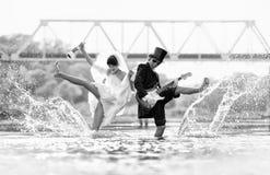De bruid en de bruidegom zijn gelukkig in de rivier Stock Afbeeldingen