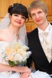De bruid en de bruidegom zitten en houden elkaar door hand Royalty-vrije Stock Afbeelding