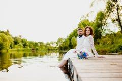 De bruid en de bruidegom zitten op een houten pijler dichtbij de vijver Stock Foto's