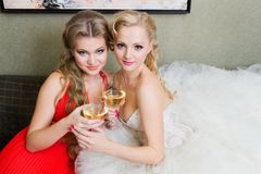 De bruid en haar bruidsmeisje met een glas wijn Stock Foto