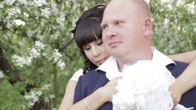 De bruid en verzorgt een romantische gang in de appelboomgaard stock footage