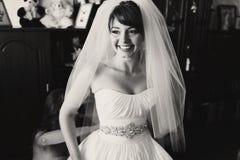 De bruid glimlacht oprecht terwijl het bruidsmeisje omhoog haar kleding dichtknoopt royalty-vrije stock foto's