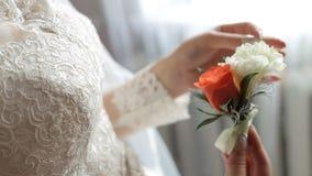De bruid houdt boutonniere op huwelijksdag stock videobeelden