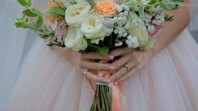 De bruid houdt een huwelijksboeket stock videobeelden