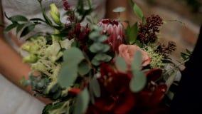 De bruid houdt een huwelijksboeket Sluit omhoog stock footage