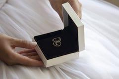 De bruid houdt trouwringdoos in hand royalty-vrije stock afbeeldingen