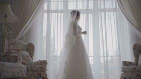 De bruid kijkt uit het venster, huwelijksdag stock videobeelden