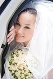 De bruid kijkt uit van de open deur van de auto Stock Foto