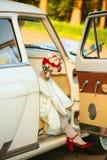 De bruid krijgt uit de auto in rode schoenen stock foto's