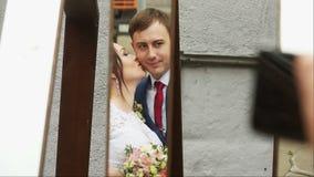 De bruid kust de bruidegom in de spiegel stock videobeelden
