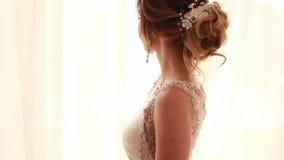 De bruid in lange huwelijkskleding gaat over ruimte stock footage