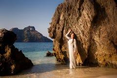 De bruid leunt op grote rots bij strand Royalty-vrije Stock Afbeelding
