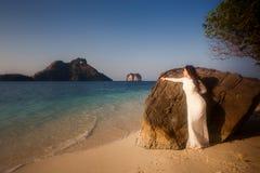 De bruid leunt op grote rots bij strand Royalty-vrije Stock Fotografie