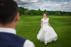 De bruid loopt om haar bruidegom op een weide te ontmoeten Royalty-vrije Stock Afbeelding