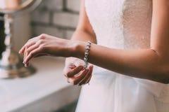 De bruid maakt een armband vast Het concept van het huwelijk kunstwerk Zachte nadruk op een hand royalty-vrije stock afbeelding