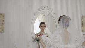De bruid met een boeket gaat naar de spiegel stock videobeelden