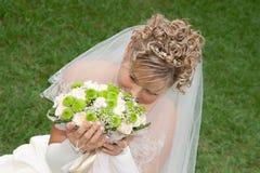De bruid met een boeket op het groene gras Royalty-vrije Stock Foto's