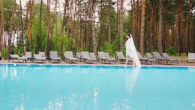 De bruid met een lange sluier loopt rond de pool Huwelijk in een luxehotel stock videobeelden
