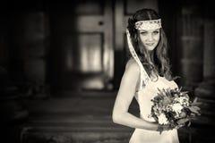 De bruid met huwelijk bloeit boeket in witte kleding met huwelijkskapsel en make-up Glimlachende vrouw die in huwelijkskleding op Royalty-vrije Stock Afbeelding