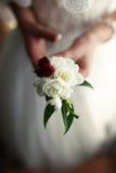 De bruid met knoopsgaten in handen Stock Foto's