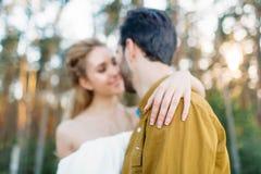 De bruid omhelst terug bruidegom ` s door haar tedere hand De vage jonggehuwden bekijken elkaar met tederheid en liefde sluit royalty-vrije stock foto