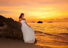 De bruid op een tropisch strand met de zonsondergang op de achtergrond Royalty-vrije Stock Afbeeldingen