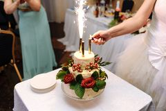 De bruid steekt vuurwerk op huwelijkscake op aan een licht tafelkleed royalty-vrije stock afbeelding