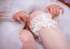 De bruid toont ons wat onder haar kleding is Stock Afbeelding