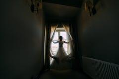 De bruid trekt de gordijnen die zich in de donkere ruimte bevinden Royalty-vrije Stock Afbeeldingen