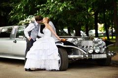 De bruid van de bruidegom adn over retro limousine Royalty-vrije Stock Fotografie
