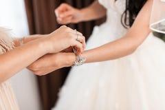 De bruid van de bruidsmeisjekleding voor de huwelijksdag Bruidsmeisjehulp met een witte kleding vóór de ceremonie Bruids luxe Stock Foto's