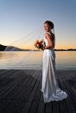 De bruid van de jonggehuwde bij zonsondergang met uitgebreide sluier Stock Foto