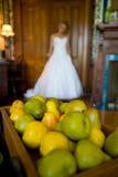 De bruid van de uit-van-nadruk achter een dienblad van peren Stock Fotografie