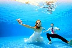 De bruid in witte kleding en de bruidegom zwemmen en stellen onderwater op camera bij de bodem van de pool in duidelijk blauw wat royalty-vrije stock afbeelding