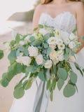 De bruid in witte kleding houdt een boeket met rozenbloemen en eucalyptustakken Huwelijksdag en ceremonie royalty-vrije stock foto