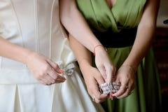De bruid zet op de armband - voorraadfoto stock afbeelding