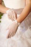 De bruid zet op een witte handschoen Stock Foto