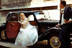 De bruid zit in een open deur van een retro auto terwijl de bruidegom behi wacht Stock Foto