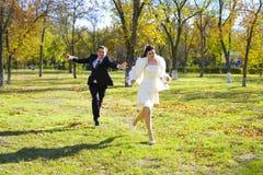 De bruidegom achtervolgt bruid Stock Afbeeldingen