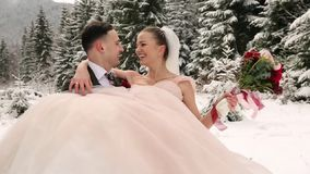 De bruidegom die gelukkige bruid spinnen die en haar houden spinnen in van hem dient de sparren net bos van het sneeuwweer tijden stock videobeelden